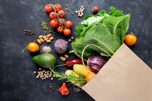 Verdure e cereali in un sacchetto di carta su una superficie nera. il concetto di un paniere di consumatori, acquisti online, cibo sano.