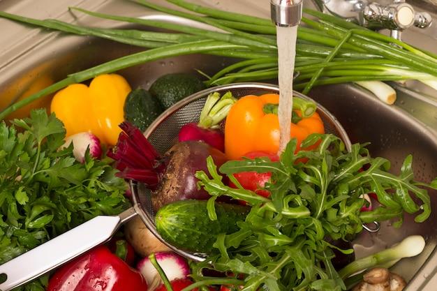 Verdure in scolapasta nel lavandino sotto l'acqua corrente.
