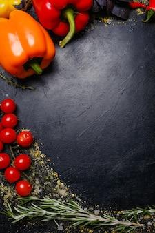 Verdure su sfondo scuro. cibo vegetariano biologico naturale. ingredienti del pasto. mangiare sano e corretto
