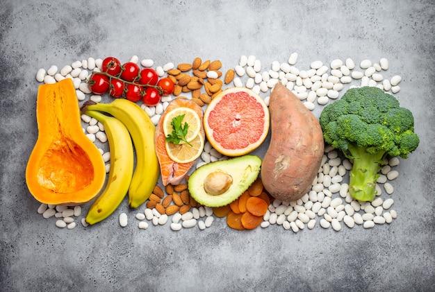 Verdure, frutta e alimenti contenenti potassio su sfondo grigio pietra, vista dall'alto. fonti naturali di potassio, vitamine e micronutrienti per una dieta sana ed equilibrata e la prevenzione dell'avitaminosi