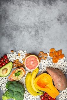 Verdure, frutta e alimenti contenenti potassio, sfondo di pietra, vista dall'alto, spazio per il testo. fonti naturali di potassio, vitamine e micronutrienti, dieta sana ed equilibrata, prevenzione dell'avitaminosi