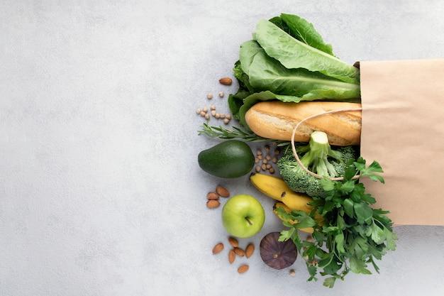 Verdure, frutta, pane in un sacchetto di carta su grigio