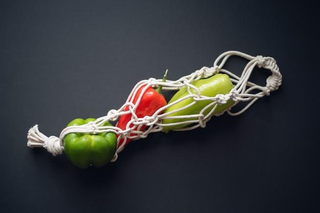 Verdure e verdure in un sacchetto di corda su uno sfondo scuro vista dall'alto