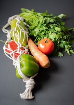 Verdure e verdure in un sacchetto di corda su uno sfondo scuro