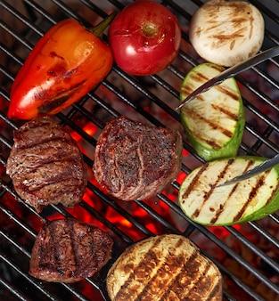 Verdure e carne sfrigolante alla griglia con fiamme, primi piani
