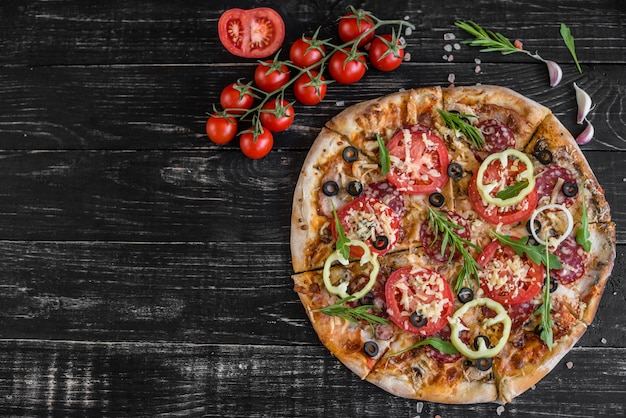Pizza di verdure, funghi e pomodori su un fondo di legno nero. può essere usato come sfondo