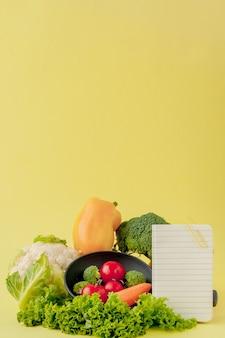 Verdure e notebook con copia spazio su sfondo giallo