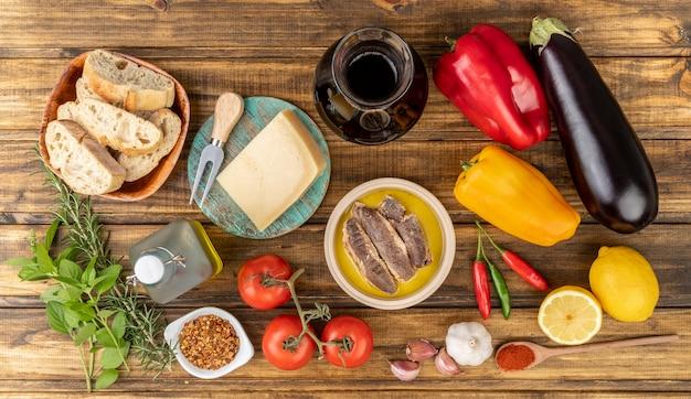Verdure, olio d'oliva, pane, formaggio, pesce e vino e verdure sul tavolo di legno. cucina mediterranea.