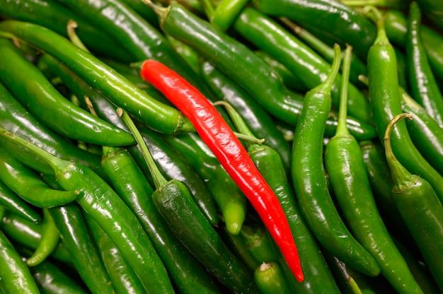 Verdure una rossa e mucchio peperoncini caldi verdi come sfondo