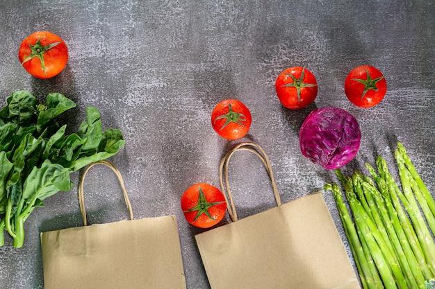 Verdure e borse della spesaverdure e cereali in un sacchetto di carta su sfondo nero