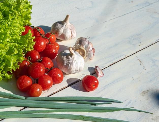 Verdure e spezie su un tavolo con luce naturale e vista dall'alto.