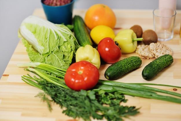 Verdure - pomodori, cipolle, peperoni, cetrioli, verdure su un tavolo di legno.