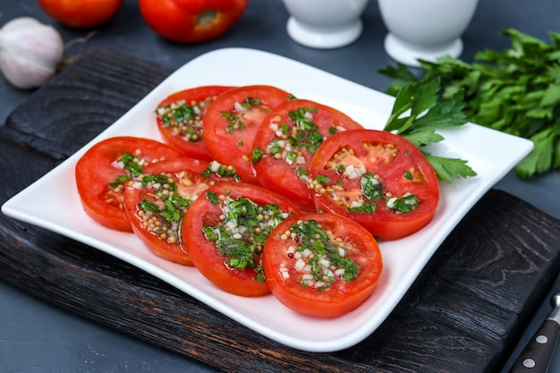 Antipasto vegetariano di pomodori con aglio, prezzemolo, condito con miele e olio d'oliva nel piatto sulla superficie scura, primo piano, formato orizzontale