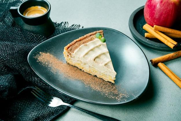 Crostata di mele vegetariana con cannella e menta su una banda nera in una composizione con caffè su un panno grigio. dessert sano senza zucchero