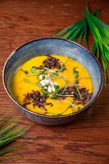 Zuppa di crema autunnale vegetariana con superficie alle erbe.
