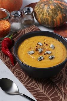 Zuppa cremosa di zucca autunnale vegetariana con lenticchie rosse su piatto scuro. avvicinamento. formato verticale