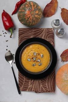 Zuppa cremosa di zucca autunnale vegetariana con lenticchie rosse su superficie grigia. vista dall'alto. formato verticale.