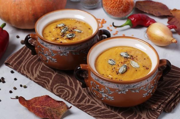 Purea di zuppa di zucca autunnale vegetariana con lenticchie rosse in due ciotole sul tavolo grigio. formato orizzontale. avvicinamento