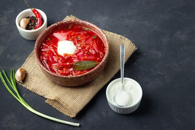 Zuppa vegetariana di barbabietola rossa - borscht con panna acida su sfondo di pietra nera.