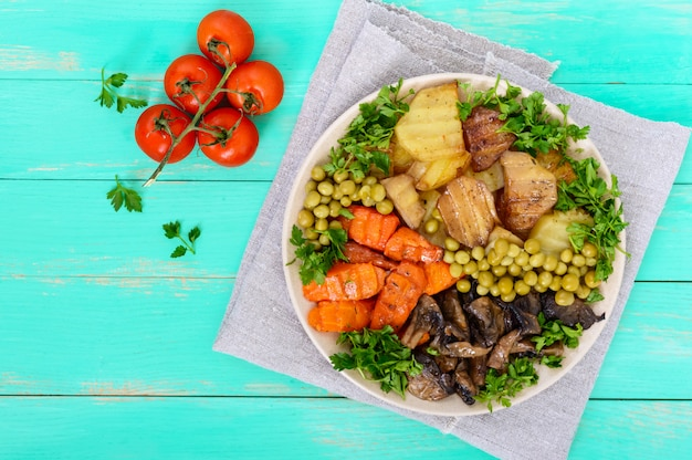 Colazione vegetariana: verdure al forno (patate, carote), funghi, piselli su un piatto