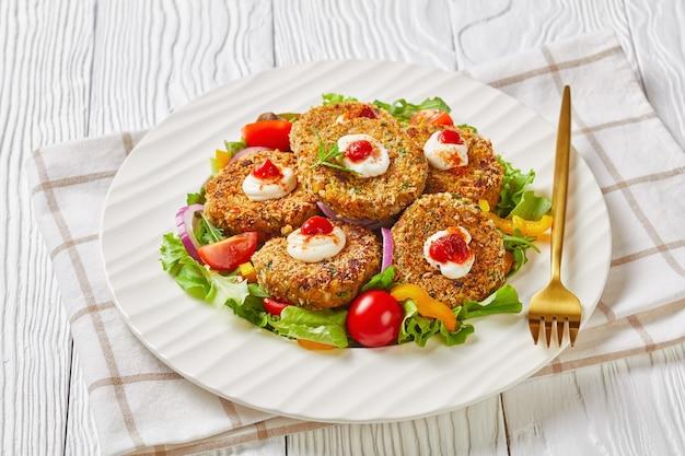 Hamburger vegetariani, polpette di legumi, cipolla e verdure servite su un piatto bianco con insalata fresca e salsa di pomodoro, vista orizzontale dall'alto