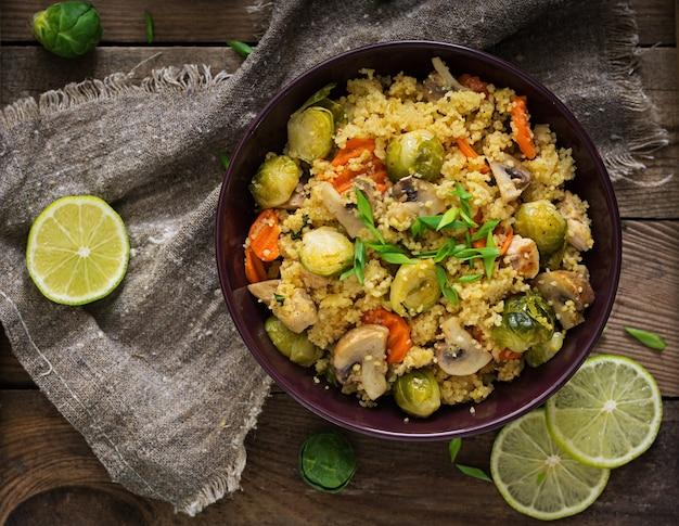 Insalata di couscous vegetariana con cavoletti di bruxelles, funghi, carote e spezie
