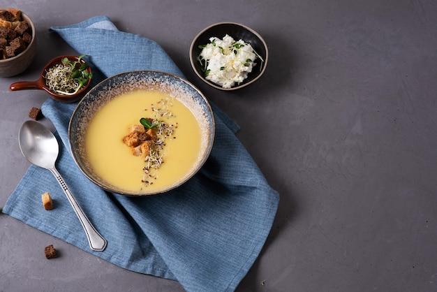 Zuppa di crema vegetariana su sfondo grigio, zuppa di purea di zucchine e zucca decorata con crostini di pane e microgreens, concetto di cibo sano.