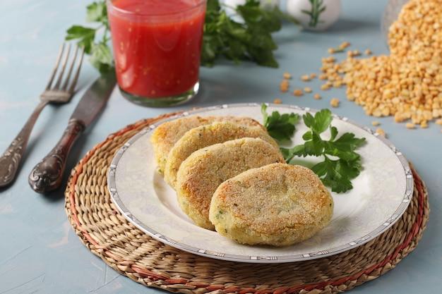 Cotolette vegetariane di piselli in un piatto e succo di pomodoro su sfondo blu