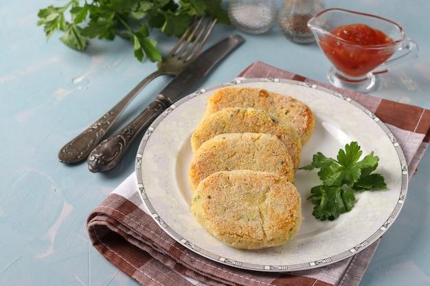 Cotolette vegetariane di piselli e semolino in un piatto con salsa, superficie blu, primo piano, copia dello spazio