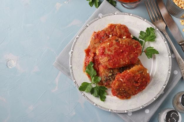 Cotolette vegetariane di piselli e semolino in salsa di pomodoro in un piatto sulla superficie blu, vista dall'alto, copia dello spazio