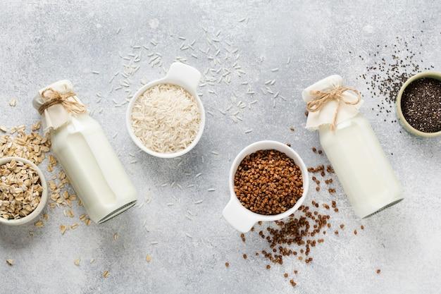 Latte dietetico vegetariano di riso ai cereali, grano saraceno e avena, tre tipi di fatti in casa su una tendenza del cemento grigio.