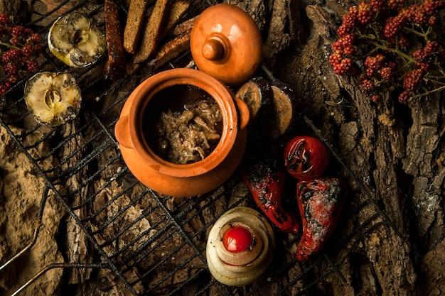 Piatto vegetariano in una pentola di terracotta con verdure arrostite alla griglia su uno sfondo di corteccia d'albero
