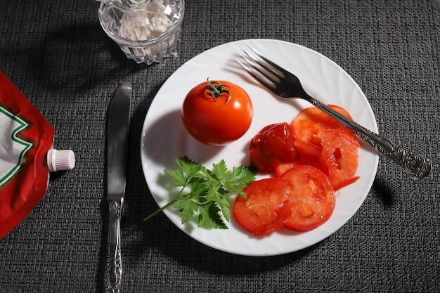 Piatto vegetariano di pomodoro rosso fresco con ketchup e foglio di verde su piatto bianco