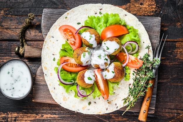 Falafel vegetariano con verdure e salsa tzatziki su una tortilla di pane. fondo in legno scuro. vista dall'alto.