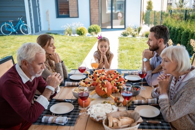 Famiglia vegetariana. persone concentrate sedute a tavola tenendo gli occhi chiusi