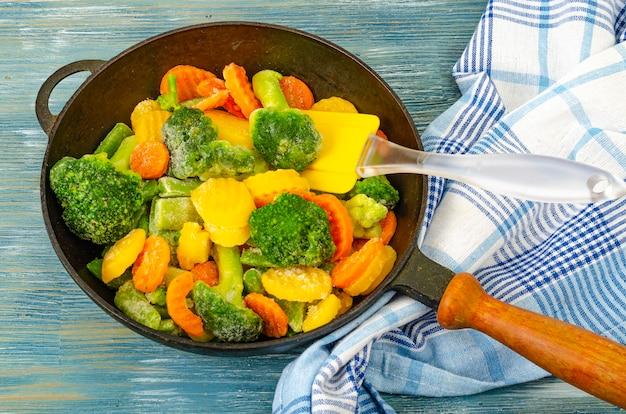 Cibo vegetariano. mix di verdure fresche congelate per friggere su fondo di legno blu. foto di studio