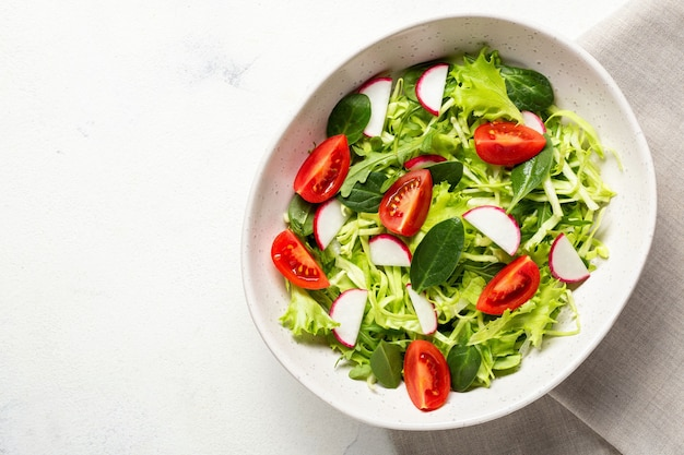 Insalata fresca vegetariana. cibo sano, pranzo dietetico. vista dall'alto su uno sfondo bianco.