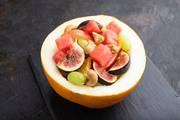 Macedonia di frutta vegetariana di anguria, uva, fichi, pera, arancia, anacardi su tavola di ardesia.