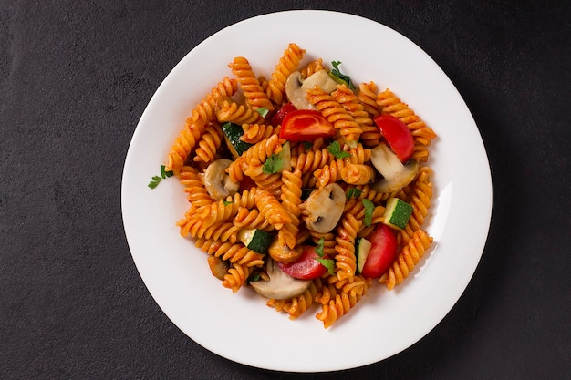 Fusilli vegetariani con zucchine, pomodori e funghi, in un piatto bianco, su sfondo grigio
