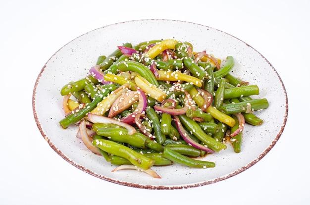 Piatto vegetariano a base di fagiolini con cipolle rosse sottaceto e semi di sesamo. foto dello studio.