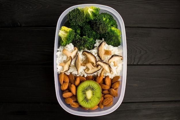 Pranzo vegetariano nella casella su fondo di legno nero.vista dall'alto.spazio copia.ingredienti alimentari sani.