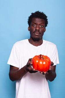 Persona vegetariana che tiene in mano un peperone rosso