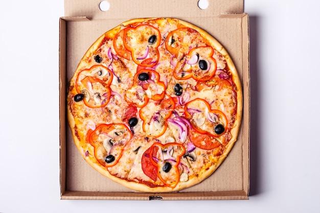 Pizza vegetariana con pomodoro, peperone dolce e olive in scatola di imballaggio su sfondo grigio.