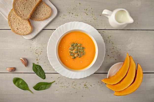 Zuppa di crema di zucca vegetariana in una ciotola bianca decorata con semi piatti adagiati su fondo di legno bianco.