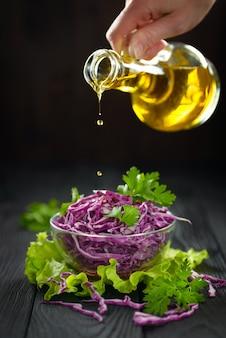 Insalata vegetariana di cavolo rosso che versa con olio d'oliva