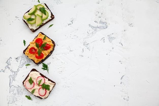 Pane tostato vegetariano di segale con ricotta, hummus, avocado, ravanello e pomodoro su sfondo bianco, copia-spazio, vista dall'alto