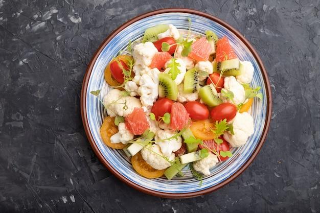Insalata vegetariana di cavolo cavolfiore, kiwi, pomodori, germogli microgreen su fondo nero