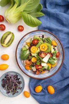Insalata vegetariana di cavolo pac choi, kiwi, pomodori, kumquat, germogli microgreen su una superficie di cemento bianco e tessuto di lino blu