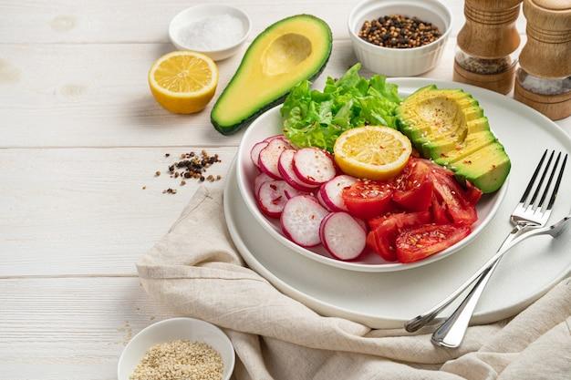 Insalata vegetariana con verdure fresche su un tavolo di legno bianco