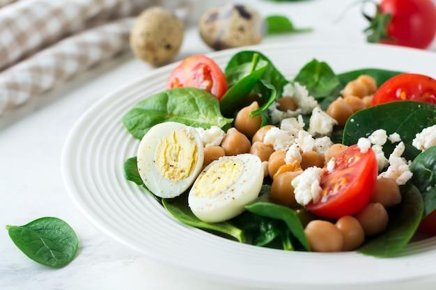 Insalata vegetariana con spinaci, ceci, pomodorini, uova e formaggio feta e limone su sfondo chiaro.